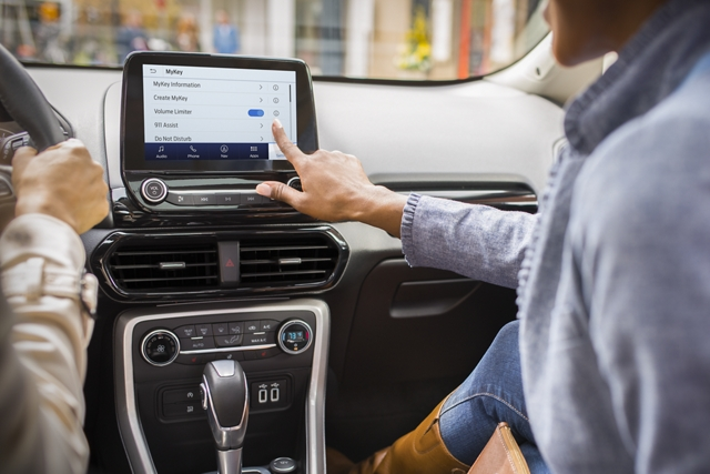 A woman using the center touchscreen in a 2020 Ford EcoSport