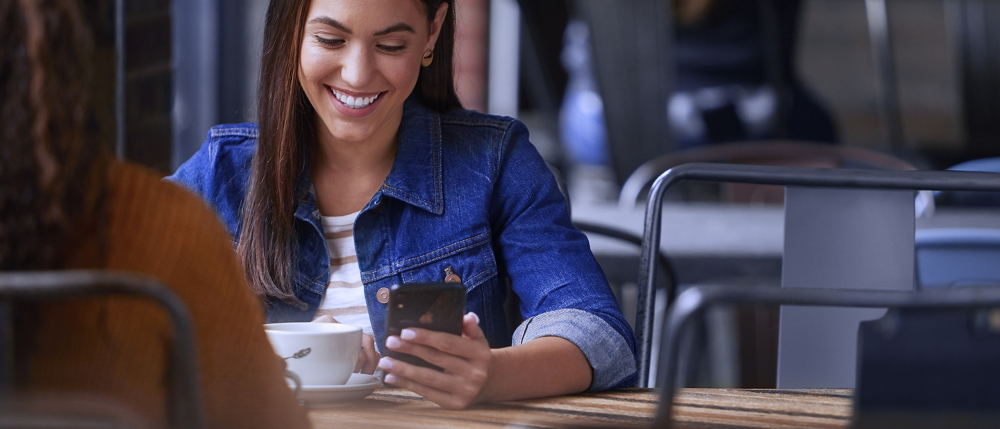 Woman sits in coffee shop and looks at FordPass App on her smartphone