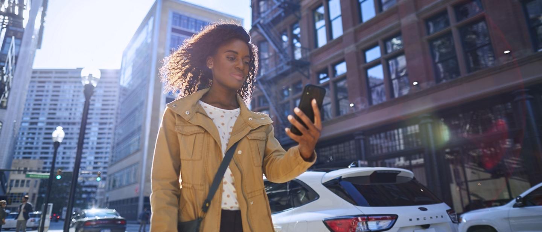 Woman walks on city sidewalk and uses her smartphone