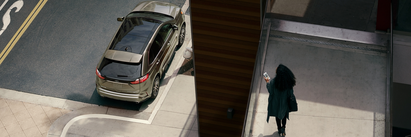 Woman holds a smartphone on a walkway overlooking her 2020 Ford Edge parked on the street below