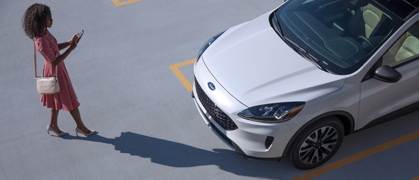 A woman approaches her 2020 Star White Ford Escape holding her smartphone