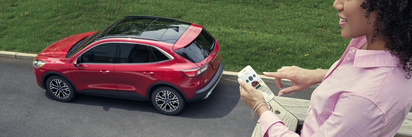 Woman holds a smartphone on a porch overlooking her 2020 Rapid Red Ford Escape on the street below