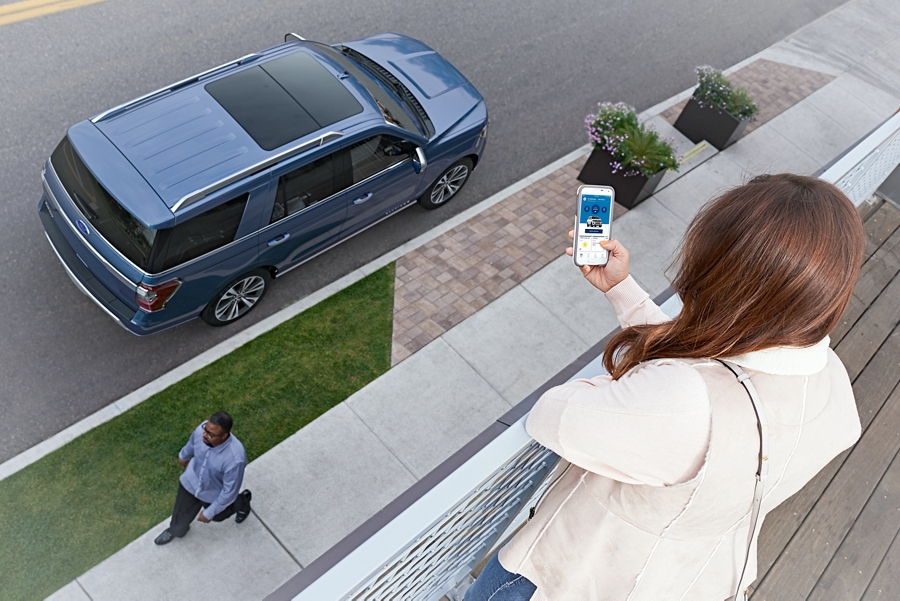 2020 Ford Expedition parked on city street with fordpass seen on phone