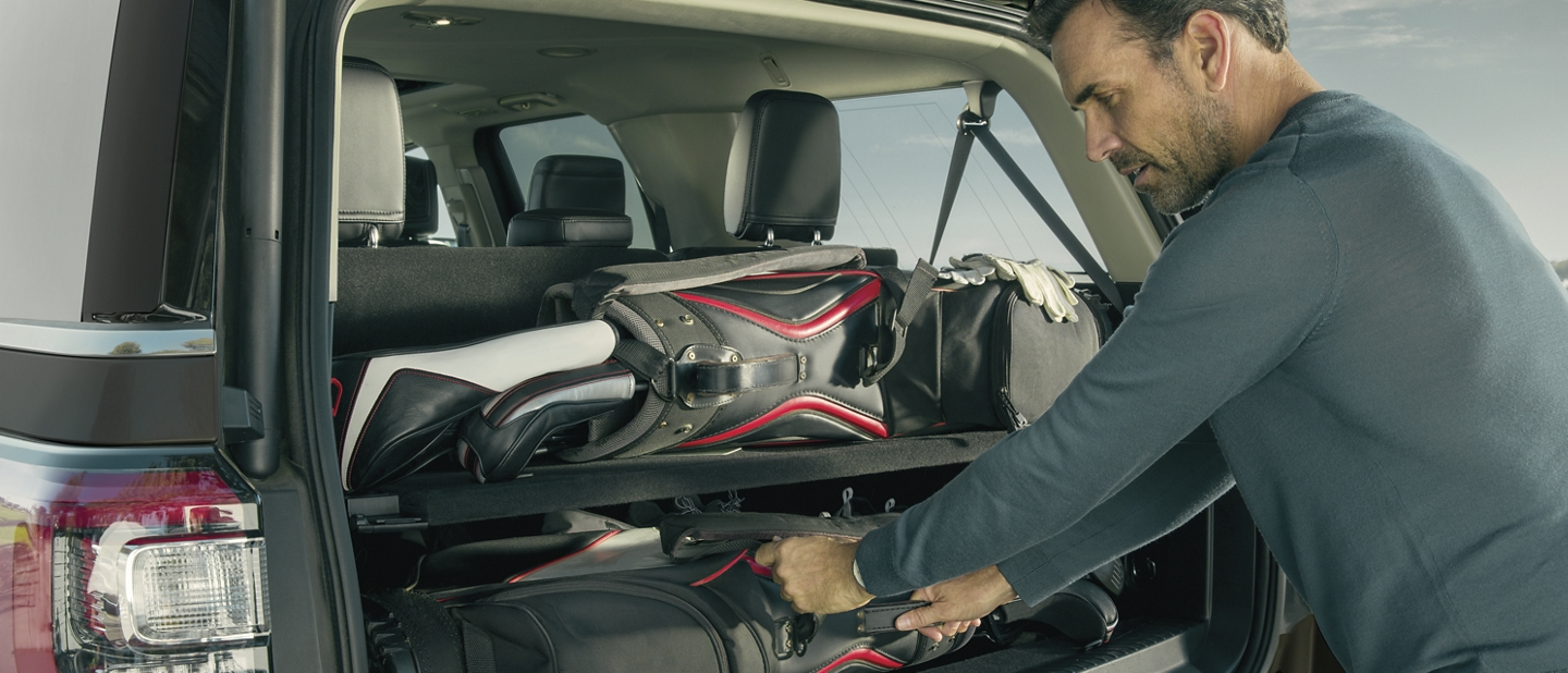 Man loading cargo into rear space of 2020 Ford Expedition