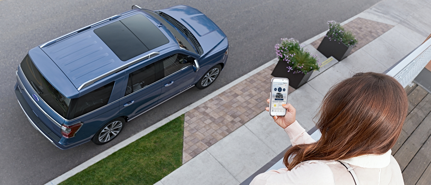 Woman holds a smartphone on a porch overlooking her blue Ford Expedition parked on the street below