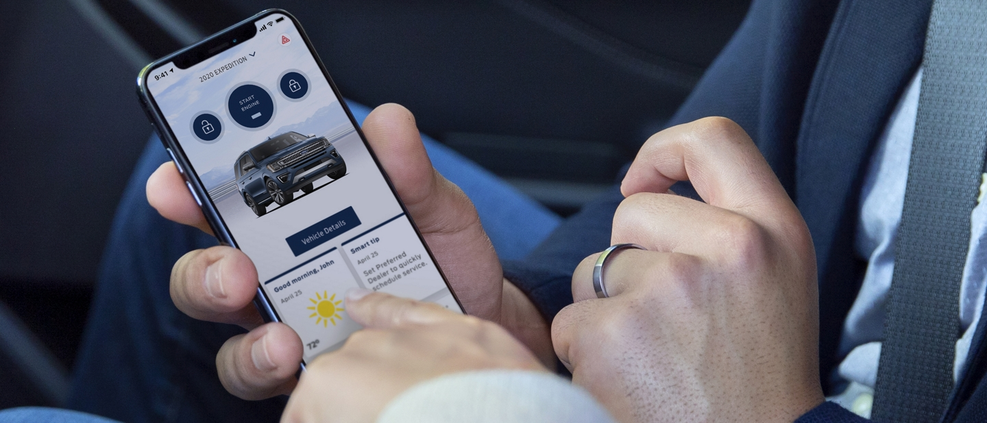 A woman points out features within the FordPass app displayed on a mans smartphone