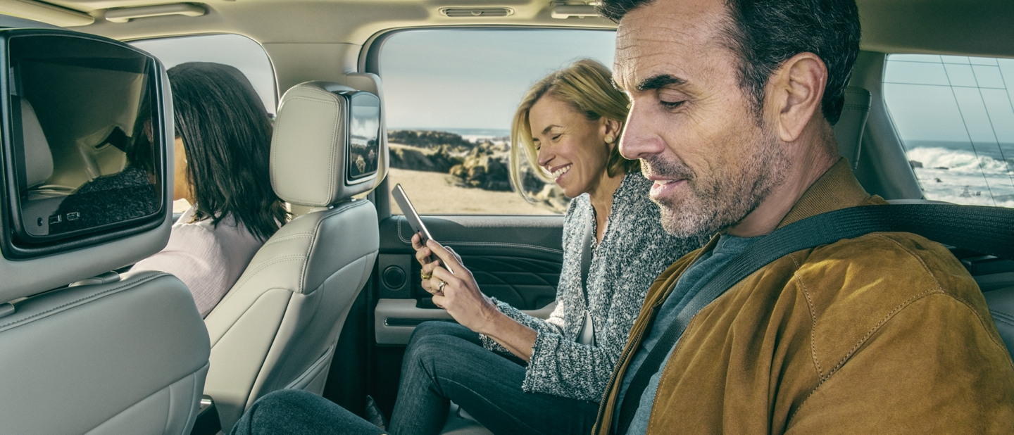 A man and a woman use WiFi devices in the back seat of a Ford vehicle