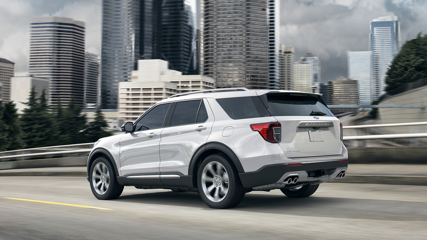 A 2020 Explorer in Star White drives down the highway