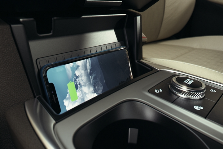 An Iphone laid sideways on the available wireless charging pad in the center console of a 2020 Explorer