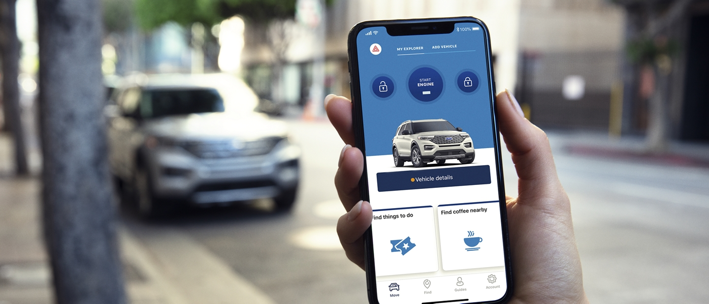 A person holds a phone with the FordPass app open with the 2020 Ford Explorer in the background