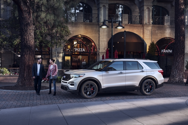 Two people holding hands next to a 2020 Explorer S T in star white