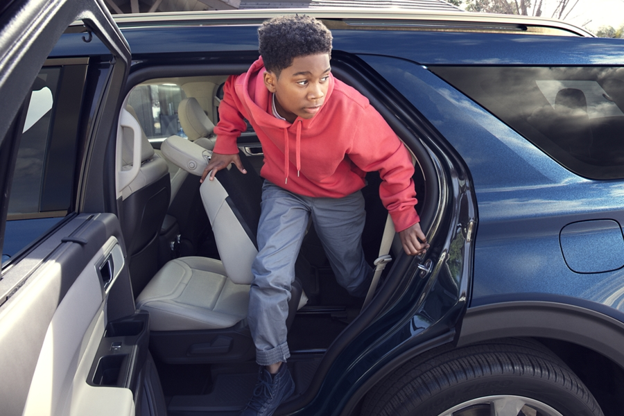 A kid getting out of the back of a 2020 Explorer