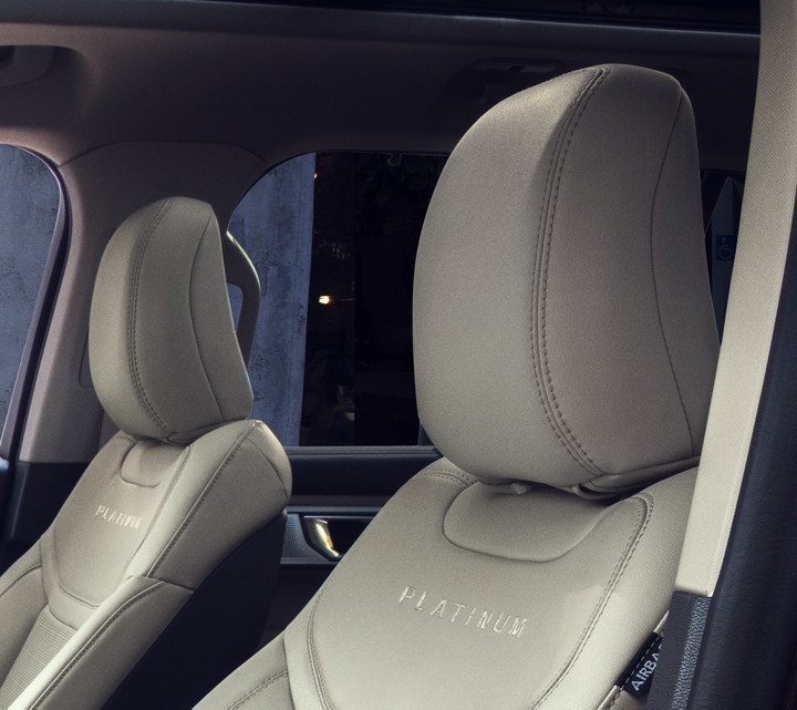 Explorer Platinum tri diamond perforated leather seating surfaces with accent stitching in Light Sandstone