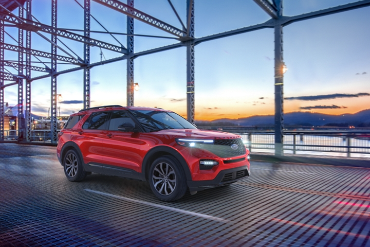 A 2020 Explorer S T in Rapid Red crossing a bridge