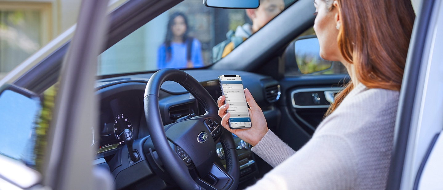 A woman holds a smartphone displaying the Schedule Service menu as she sits in the drivers seat of her Ford Explorer