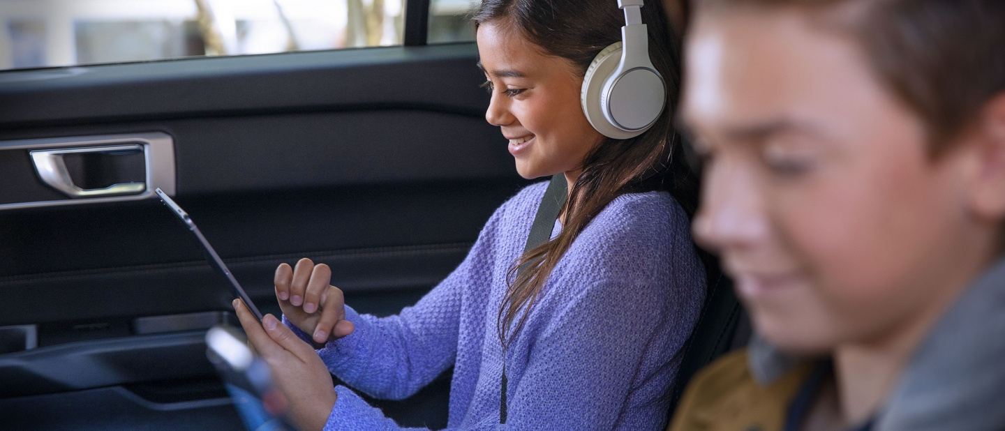A girl and a boy use WiFi devices in the back seat of a Ford vehicle