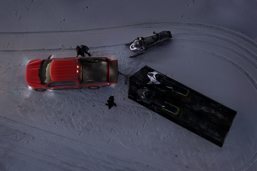 People loading snowmobiles onto a trailer attached to a 2021 Ford F one fifty with zone lighting