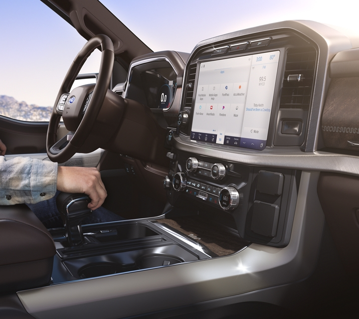 A woman in the drivers seat of a 2021 Ford F one fifty