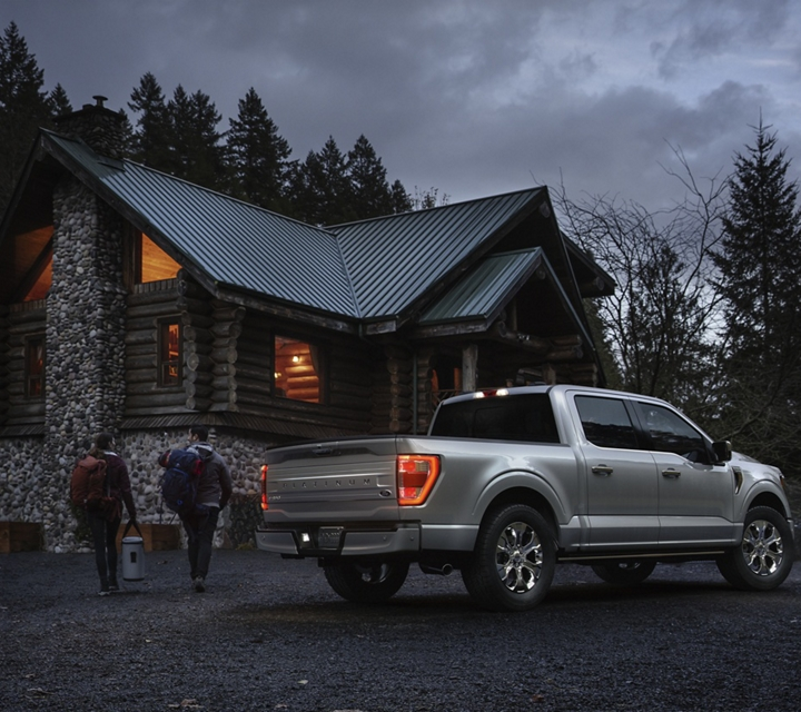 Two people at a remote cabin with a 2021 Ford F one fifty parked nearby