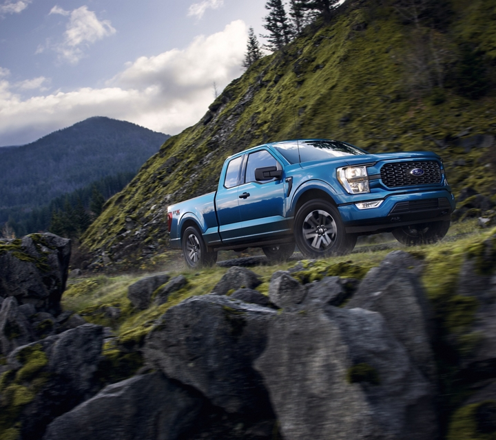2021 Ford F one fifty rounding a curve on a scenic mountain road