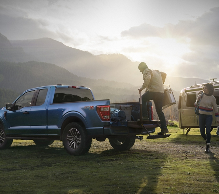 A couple loading camping gear into the bed of their 2021 Ford F one fifty near their campsite