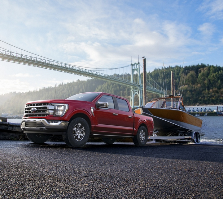 A 2021 Ford F one fifty backing up a boat into water