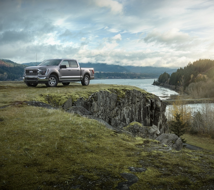 A 2021 Ford f one fifty on a grassy cliff near a lake