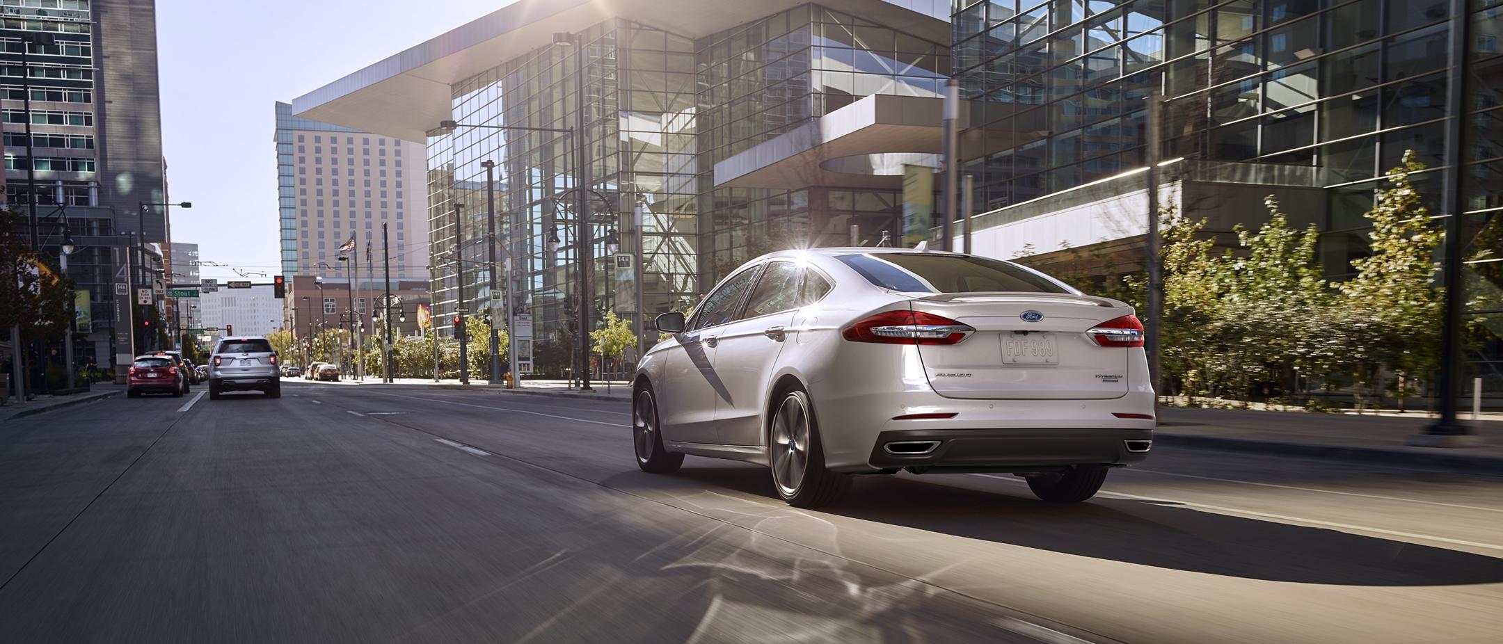 A 2020 Ford Fusion Titanium in White Platinum metallic tri coat being driven down a city street