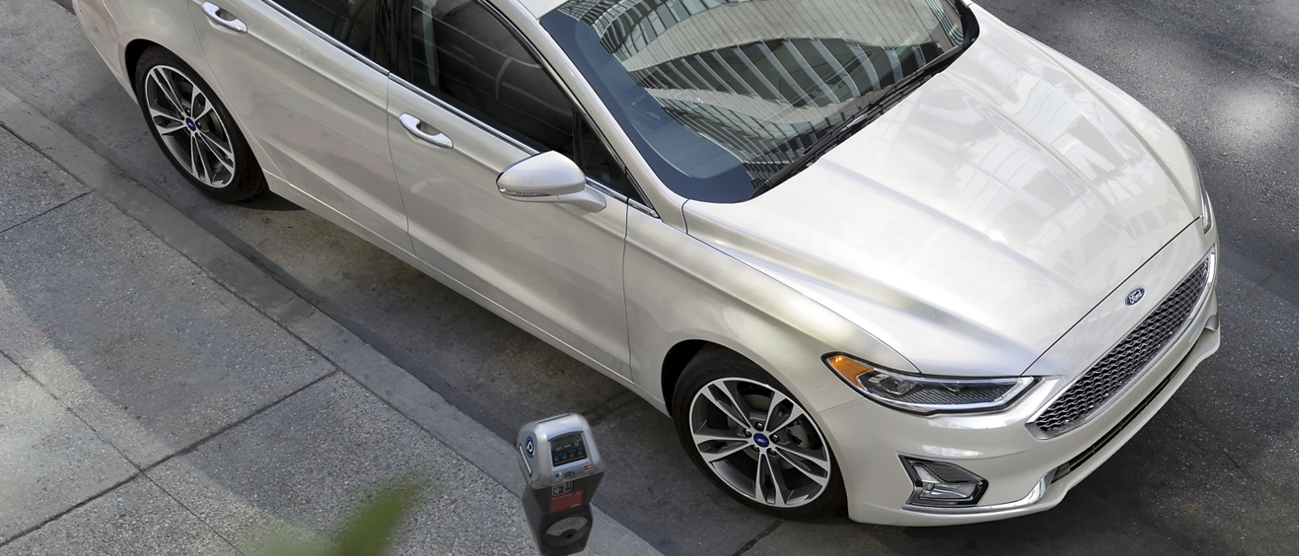 2020 Ford Fusion Plug in Hybrid Titanium pulling away from a parking meter