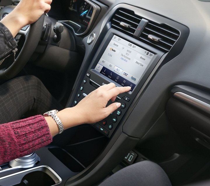 2020 Ford Fusion interior with a passenger using sync 3 on the L C D touchscreen
