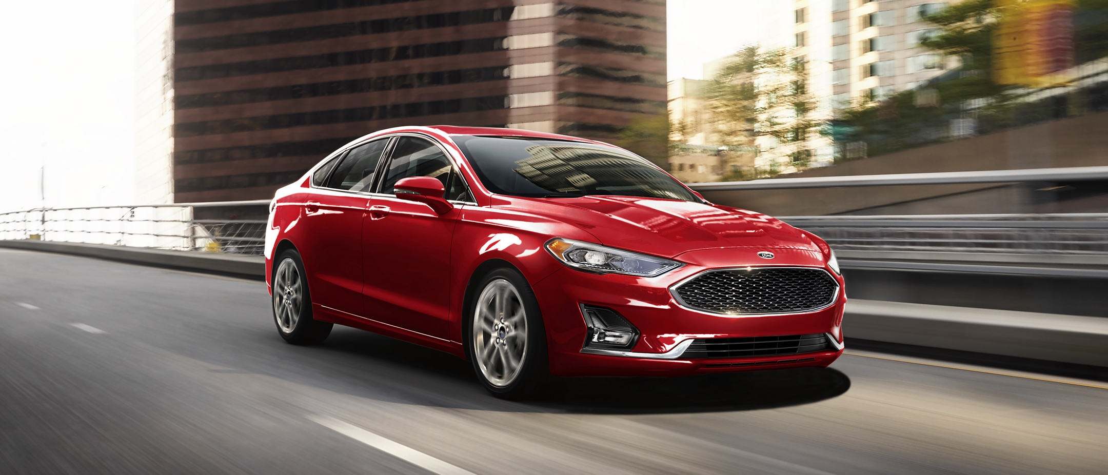 A 2020 Ford Fusion Hybrid in Rapid Red being driven down a city street