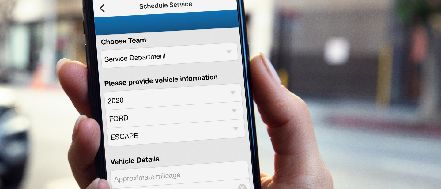 A hand holds a smartphone displaying the Schedule Service menu in the FordPass App