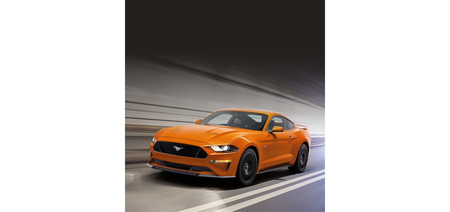 A 2020 Ford Mustang G T Premium Fastback shown in Twister Orange on the road