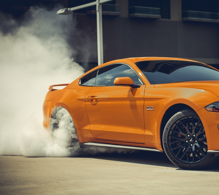 2020 ford Mustang in twister orange with the G T Performance Package and spinning tires