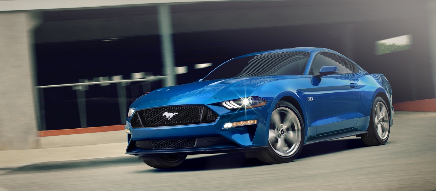 A 2020 Ford Mustang G T Premium in Velocity Blue exiting a parking structure