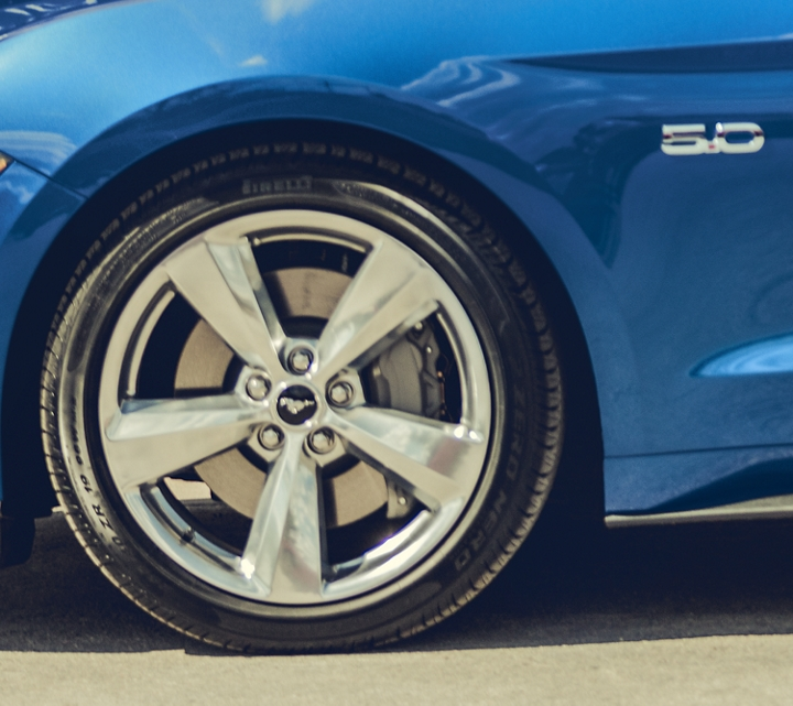 Men walking away from a 2020 Ford Mustang with 19 inch by eight point 5 inch polished aluminum wheels