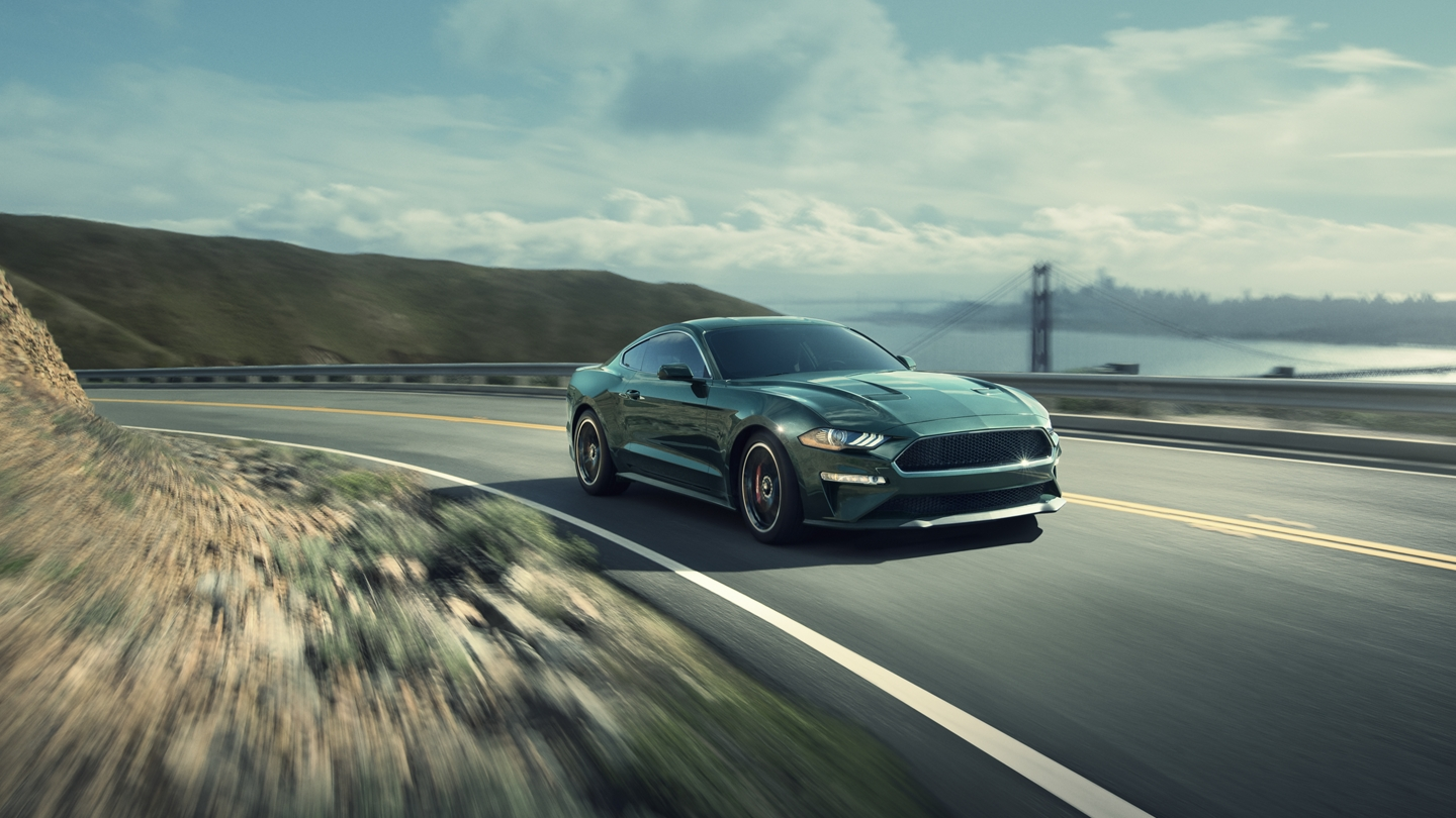 2020 Ford Mustang BULLITT rounding a corner with a body of water and bridge in the background