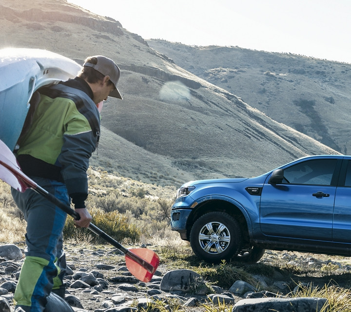 A kayaker near a stream walking towards a 2019 Ford Ranger in Lightning Blue with optional bed mounted rack accessory