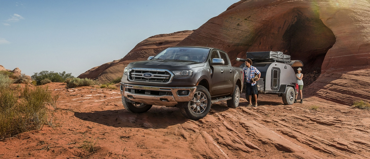 2019 Ford Ranger with camper trailer on hilly desert terrain