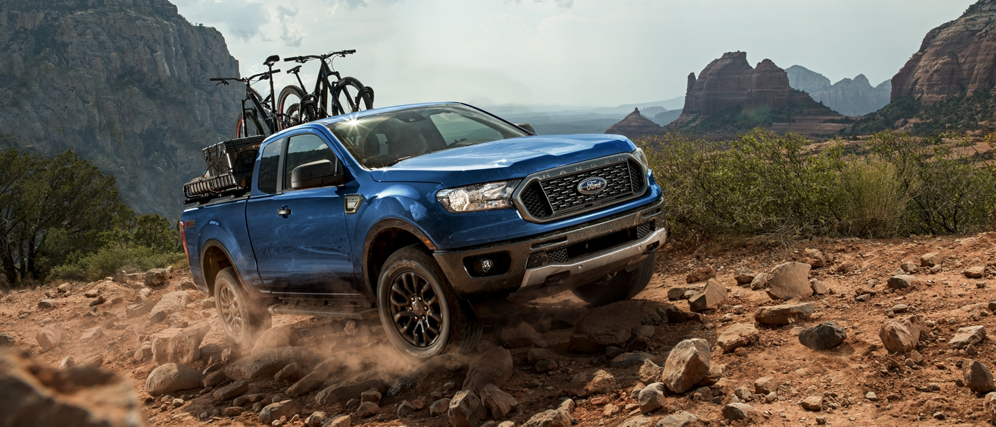 2019 Ford Ranger on rock covered terrain with trail bikes on pickup bed rack