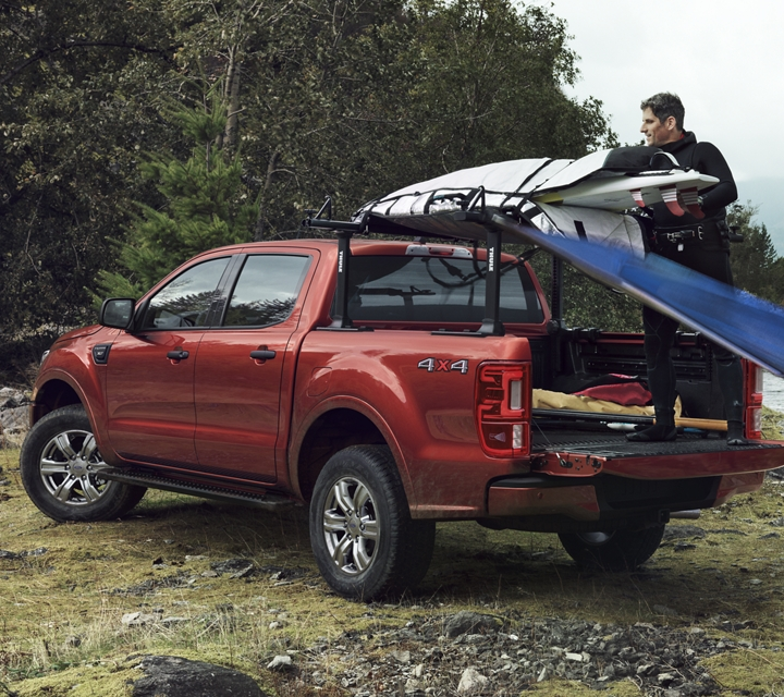 2020 Ford Ranger shown in Rapid Red Metallic Tinted Clearcoat loaded with kayaks on a lake