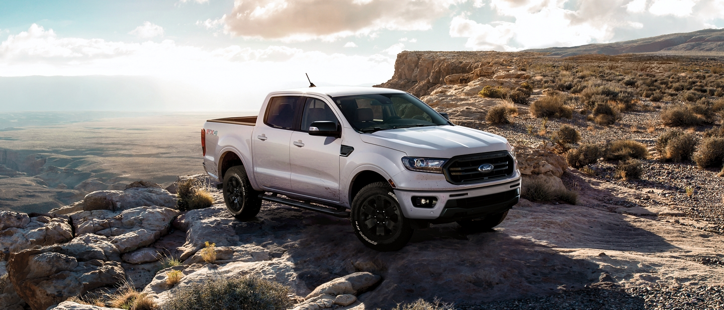 By the edge of a cliff is a 2020 Ford Ranger LARIAT Super Crew in White Platinum Tri Coat Metallic and Black Appearance Package