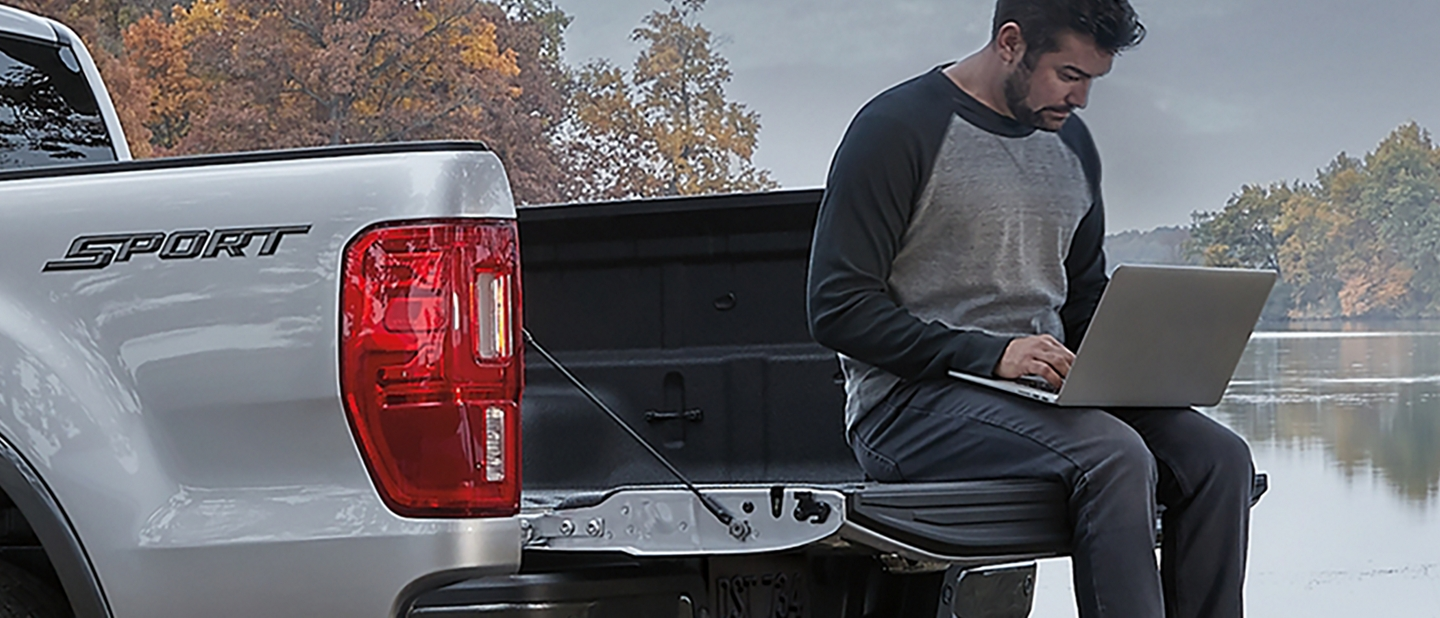 A man sits on the open tailgate of his 2020 Ford Ranger and uses a laptop