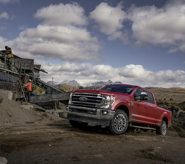 A 2020 Super Duty on a construction site with snow capped mountains in the background