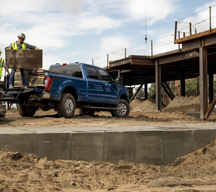 A Construction worker loads concrete forms into the bed of a 2020 Super Duty