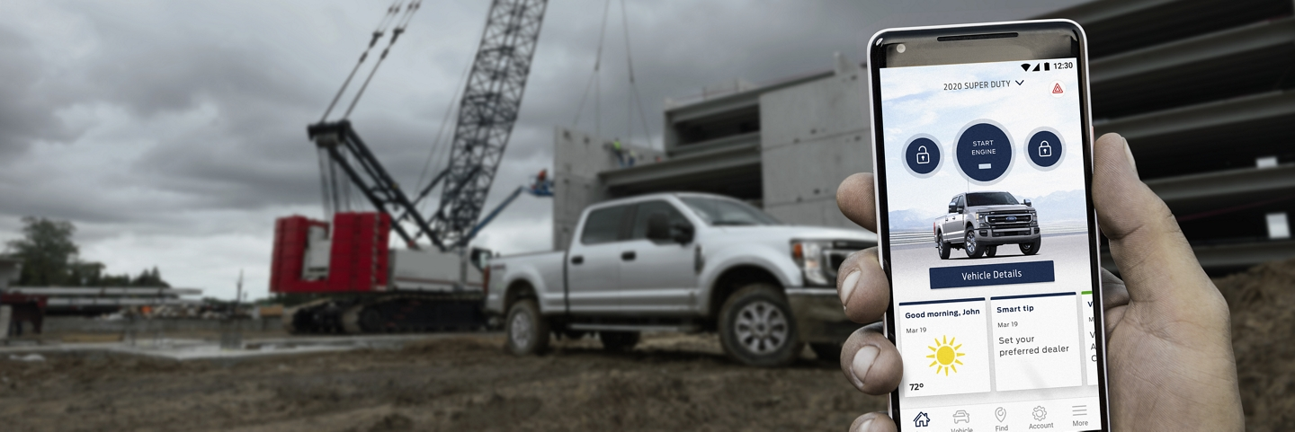 A hand holds a smartphone displaying a 2020 Ford Super Duty pickup in the FordPass App