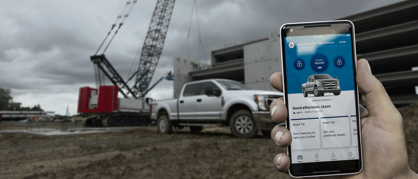 Hand holding a smart phone on a job site with a 2020 Ford Super Duty in the background