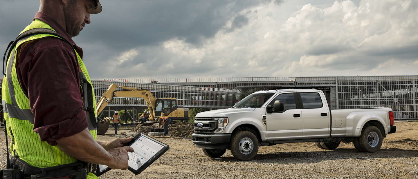 A contractor stands on a worksite and interacts with a tablet in front of his Super Duty pickup