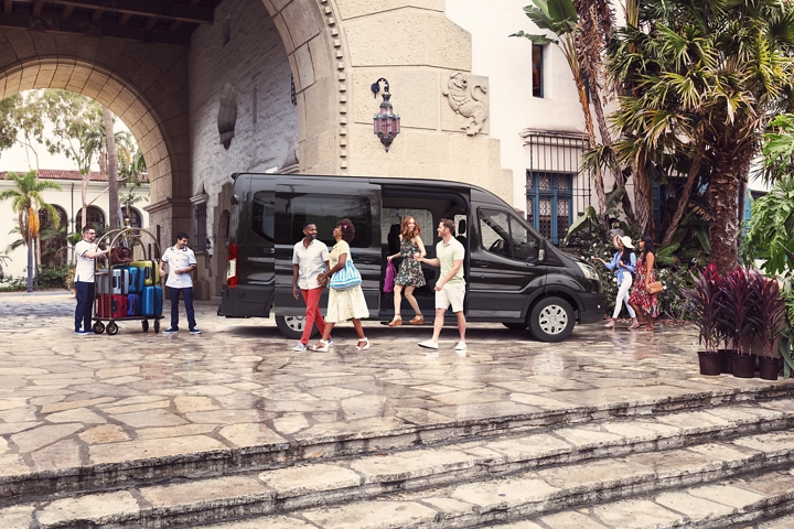 A crowd of passengers and some luggage is seen near a parked 2020 Transit Passenger Van