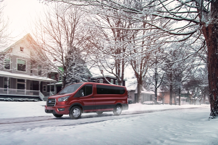 A 2020 Ford Transit being driven on a suburban street in the snow